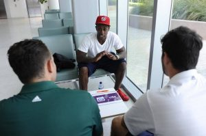 Former NFL player Phillip Buchanan talks to UM students Nolan Chasten, left, and Chris Guerrero, right, about a new app. (Photo Credit: Logan Riely)